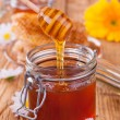 Honey in jar with honeycomb and wooden drizzler — 图库照片