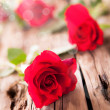 Red roses on wood — Stock Photo