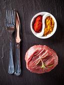 Fresh raw beef steak on black stone — Stock Photo