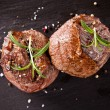 Fresh beef steaks on black stone — Stock Photo