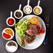 Fresh beef steak on black stone — Stock Photo