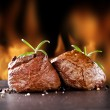 Fresh beef steaks on black stone and fire — Stock Photo #41916285