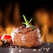 Fresh beef steak on black stone and fire — Stock Photo #41917651