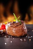 Fresh beef steak on black stone and fire — Stockfoto