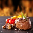 Fresh beef steak on black stone and fire — Stock Photo #43412175