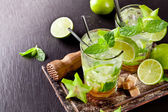 Fresh mojito drinks on black stone — Stock Photo