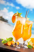 Summer drinks on stone with beach — Stock Photo