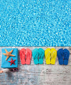 Summer accessories on wood with swimming pool surface — Stock Photo