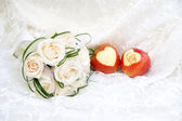 Wedding rings on apples and bouquet — Stock Photo