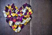 Background with a heart of rose petals for Valentine's day — Stockfoto