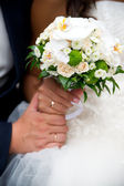 Bouquet and hands with rings — Stock Photo