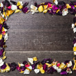Frame with dry rose petals on wooden background — Stock Photo #40484647