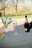 Newlywed's hands with a bouquet and a bottle of champagne — Stockfoto