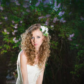 Beautiful bride in a white dress on a lilac background in spring — Foto de Stock