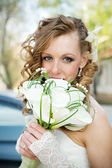 Beautiful bride in a white dress with a bouquet of calla lilies — Stock Photo