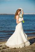 красивая невеста в белом платье на берегу реки — Стоковое фото