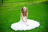 Schöne braut in einem weißen kleid auf grünem gras im sommer — Stockfoto