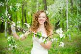 Vackra brud i en vit klänning i blommande trädgårdar under våren — Stockfoto