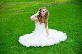 Beautiful bride in a white dress on green grass in summer — Stock Photo