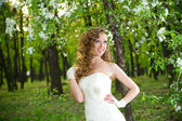 Beautiful bride in a white dress in blooming gardens in the spring — Stock Photo