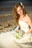 Beautiful bride in a white dress on coast of river — Photo
