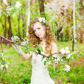 Beautiful bride in a white dress in blooming gardens — Stock Photo