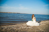 Beautiful bride in a white dress on coast of river — Stock Photo