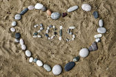 Stones on sand in shape of heart closeup — Stock Photo