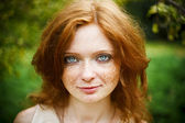 Portrait of redhead girl with blue eyes on nature — Stock Photo