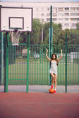 Beautiful young woman playing basketball outdoors — Stock Photo