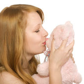 Young girl kissing a teddy bear, isolated — Stock Photo