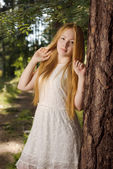 A young girl with long blond hair, standing in the forest — Stock Photo