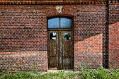 Grunge brick wall & barred door — Stock Photo