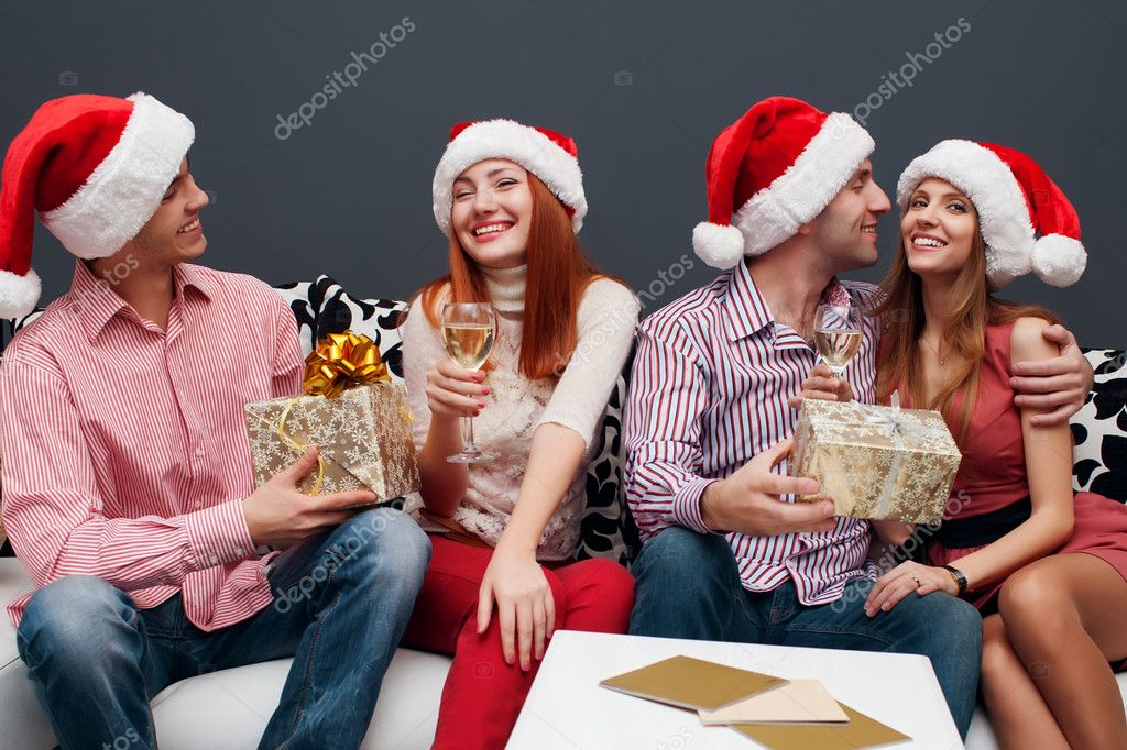 Happy friends sitting near Christmas tree with presents — Stock Photo #14133056