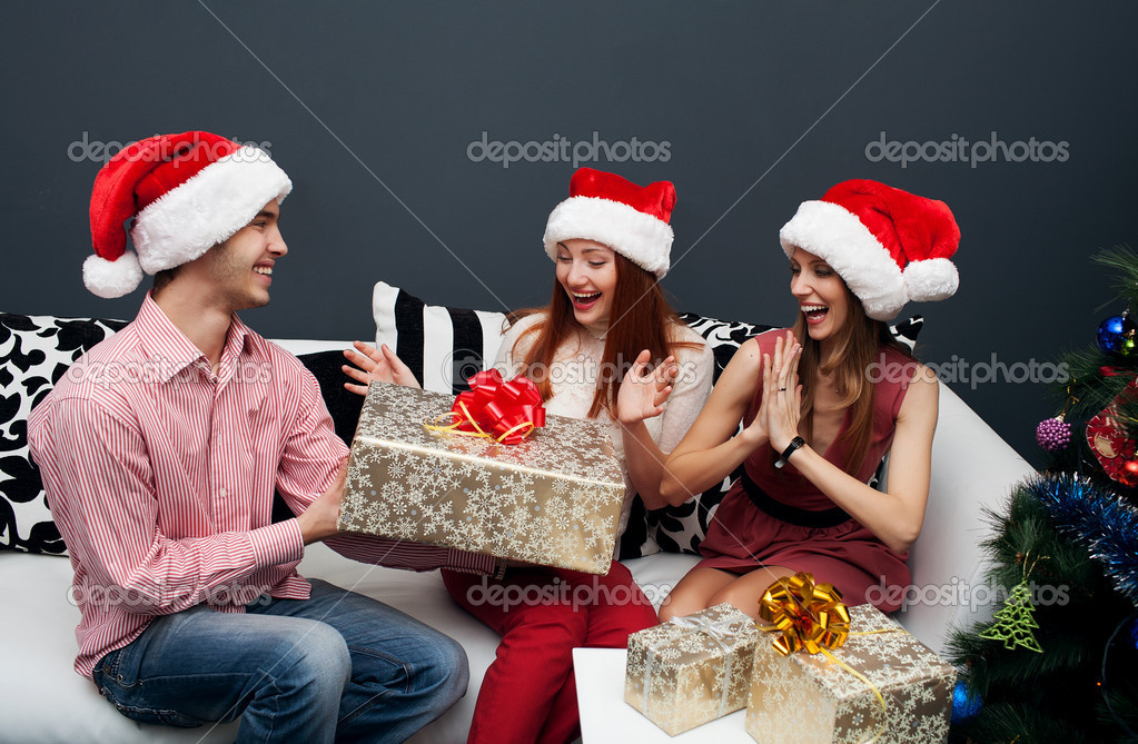 Happy friends celebrating cristmas, boy presenting a gift to his girlfriend — Stock Photo #14133060