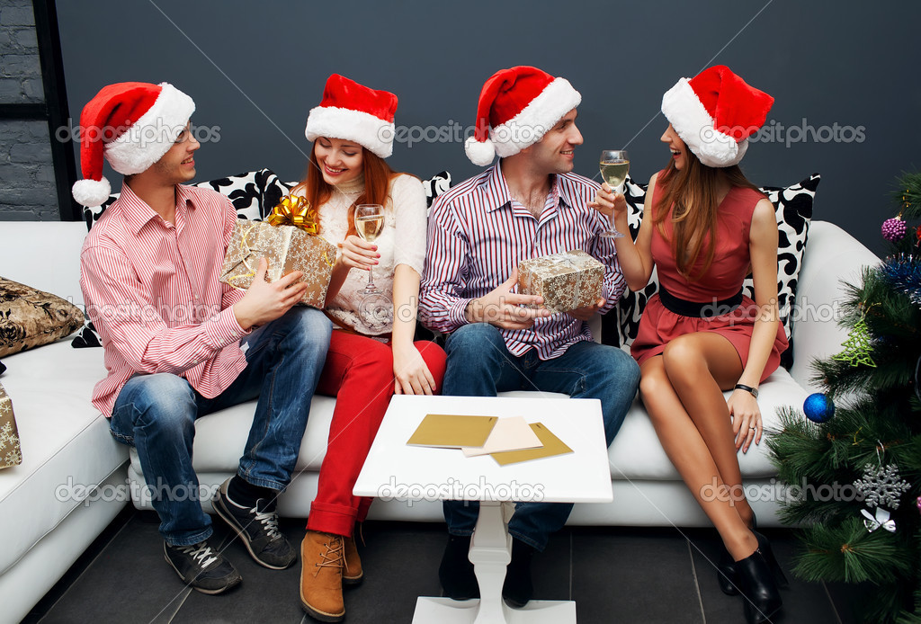 Happy friends sitting near Christmas tree — Stock Photo #14133061