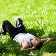 Happy guy lying on the grass and listening to music — Stock Photo