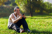 Portrait of a relaxed young man sitting on grass in park and lis — Стоковое фото