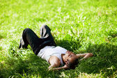 Happy guy lying on the grass and listening to music — ストック写真