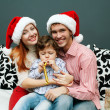 Royalty-Free Stock Photo: Happy family holding Christmas presents at home