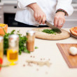 Young chef prepares a man in the kitchen — Stock Photo
