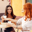 Very cute smiling women drinking a coffee sitting — Stock Photo