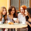 Very cute smiling women drinking a coffee sitting outside in a c — Stock Photo