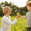 Mother and Son Having Fun. Son giving flowers to his mother — Stock Photo