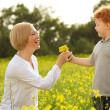Mother and Son Having Fun. Son giving flowers to his mother — Stock Photo #14554195