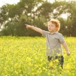 Stylish baby boy having fun outside in the field — Stock Photo