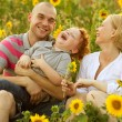 Happy family having fun in the field of sunflowers. Father hugs his son. — Stock Photo