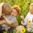 Happy family having fun in the field of sunflowers. Father hugs his son. — Stock Photo #14554723