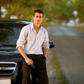 Handsome man standing on the road near his car — Stockfoto