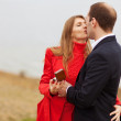 Young man romantically proposing to girlfriend and offering - Stock Photo